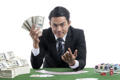 The dealer man trigeer finger invite to a gambler and show a lot. In the dealer man right hand shows a lot of banknotes And the left hand on the trigger finger Royalty Free Stock Photos