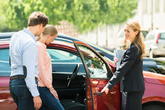 Dealer Opening Car Door For Customer. Young Happy Female Opening New Red Car Door For Customer royalty free stock image