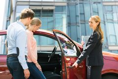 Dealer Opening Car Door For Young Couple. Smiling Female Dealer Opening Red Car Door For Young Couple royalty free stock photos