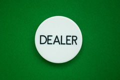 Dealer`s button. Poker dealer`s button on green cloth background Royalty Free Stock Image