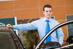 Dealer stands near a new car in the showroom. Dealer stands near a new car, car dealerships royalty free stock photo
