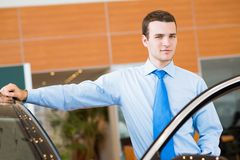 Dealer stands near a new car in the showroom. Dealer stands near a new car, car dealerships royalty free stock images