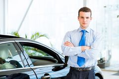 Dealer stands near a new car in the showroom Stock Image