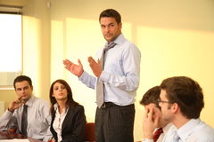 Dealing with crisis. Group of business listening to their boss during informal meeting royalty free stock photo