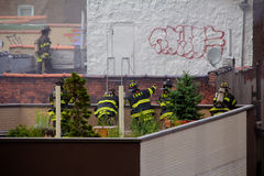 Dealing with the Fire. Group of fireman stands around figuring out the best method tackle a a raging fire on a neighboring building in Spanish Harlem Stock Images