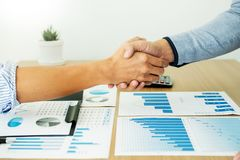 Dealing greeting and partnership meeting concept, businessmen handshaking after finishing up deal contract for both companies. Dealing greeting and partnership stock photo
