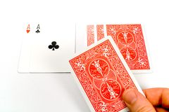 Dealing stud poker. A hand dealing a card in a round of texas hold 'em, isolated against a white background Royalty Free Stock Photo