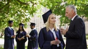 Dean die met mooi gediplomeerd wijfje dichtbij academie, carrière en toekomst spreken stock foto