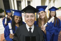Dean and graduates outside university Stock Photos