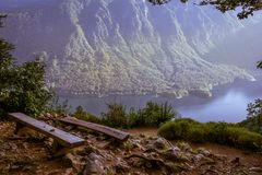 Deap blue lake Bohinjsko jezero. Landscape view of the blue lake Bohinjsko jezero from the nice viewpoint. Two wooden benches at the viewpoint. Summer in Julian Royalty Free Stock Image
