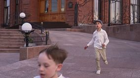 Dear amicable children play on the street. Boys in white shirts run on the street stock video footage