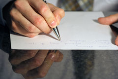 Dear Anna. Reflection of male's hand writing letter Stock Images