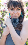 Dear chinchilla friend. Pretty young woman model with bright colorful makeup wearing summer dress, blue earrings, holding her pet chinchilla on her hands Stock Images