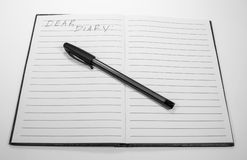 "Dear Diary. Image of diary or journal book opened to a blank page and a black pen with the written words ""Dear Diary stock photo"