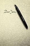 Dear jane. Leter being written in calligraphy on parchment paper with pen royalty free stock images