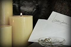 Dear John letter. A Dear John note left by some candles with a ring in the crystal dish Stock Image