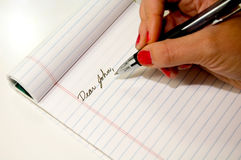Dear John Note. Woman's hand writing a Dear John letter stock photo