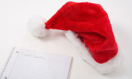 Dear Santa. Letter from child with Santa hat laying on table Stock Photo
