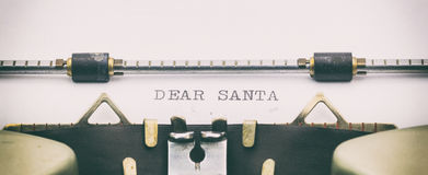 DEAR SANTA in capital letters on a typewriter sheet. Close-up of DEAR SANTA on a typewriter sheet Royalty Free Stock Photo