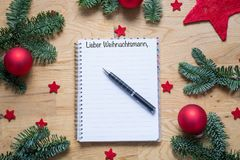 Dear Santa in German on a notepad with Christmas decorations and. Fir branches on a wooden table from above Stock Images