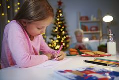 Dear Santa... Girl writing a letter to Santa Claus Royalty Free Stock Photos