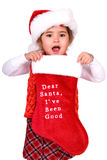 Dear Santa, I've been good. Cute child wearing a Santa hat holding up a stocking that says Dear Santa, I've been good Isolated on white Royalty Free Stock Photo