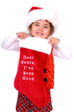Dear Santa, I've been good. Cute child wearing a Santa hat smiling and holding up a stocking that says Dear Santa, I've been good Isolated on white Royalty Free Stock Photos