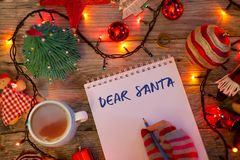 """""""Dear Santa"""" introduction on Santa's letter, Christmas background with notebook surrounded by decorations royalty free stock photos"""