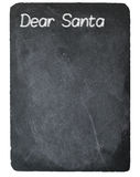 Dear Santa letter using chalk on slate blackboard. Dear Santa text message written in chalk on a chalky natural slate blackboard isolated against white Royalty Free Stock Image