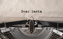 Dear Santa printed on an old vintage typewriter, close-up. Letter to Santa Claus with wishes for gifts, Christmas, New Year Stock Photo