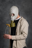 Death. Concept image of death featuring a young man wearing a gas mask and holding a wilted flower Stock Photo