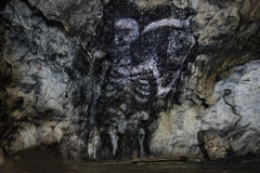 Death Cave Painting. Creepy cave painting showing Death holding a scythe in the Polovragi cave, Valcea/Gorj County, Romania, serves as a warning to turn back or Royalty Free Stock Photos