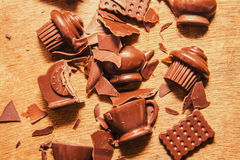 Death by chocolate. Choc overload with broken flakes of choc chip chunks in shattered pieces of cups and dessert fragments.  Death by chocolate Royalty Free Stock Photos