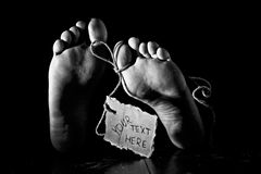 Death concept. Feet of a corpse on a wooden floor with cardboard tag on rope and handwritten text. Grunge processing, black&white image with grain added Royalty Free Stock Image