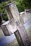 Death concept. Old stone grave cross in cold lighting Royalty Free Stock Photography