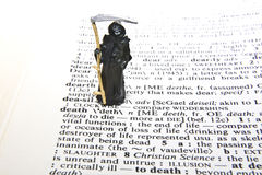 Death Definition. Miniature of Grim Reaper with definition of death Stock Images