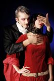 Death kiss. Portrait of a beautiful couple in medieval costumes with vampire style make-up. Shot in a studio Royalty Free Stock Photo