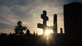 Death life concept. cemetery crosses sunlight glints from behind the graves lifestyle at sunset cross silhouette. Death life concept. cemetery crosses sunlight stock video footage