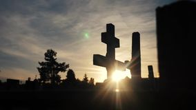 Death life concept. Cemetery crosses sunlight glints from behind the graves at sunset cross lifestyle silhouette. Death life concept. Cemetery crosses sunlight stock video