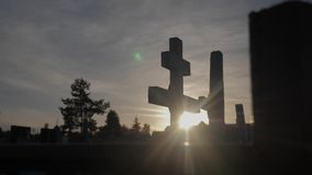 Death life concept. Cemetery crosses sunlight glints from behind the graves at sunset lifestyle cross silhouette. Death life concept. Cemetery crosses sunlight stock footage