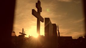 Death life concept. Cemetery crosses sunlight glints from lifestyle behind the graves at sunset cross silhouette stock video footage