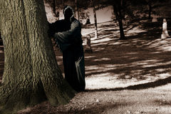 Death lurking in the cemetery. Death lurking behind a tree in the cemetery Royalty Free Stock Photo
