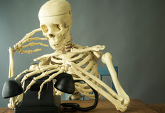 Death Making a Phone Call. A skeleton or death making a phone call, whose number is up Royalty Free Stock Images