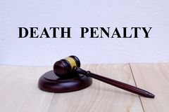 Death Penalty written on the wall with gavel on wooden background. Law concept.  stock photo
