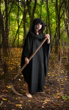 Death with scythe. Death with horror make-up in black robe with scythe waiting in the forest royalty free stock photo