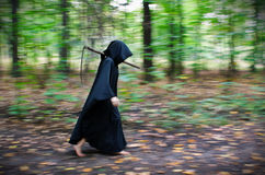 Death with scythe. Faceless Death in black robe with scythe walking through the forest stock images