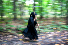 Death with scythe running. Faceless Death in black robe with scythe running through the forest Stock Photos