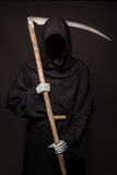 Death with scythe standing in the dark. Halloween. Studio portrait on black background Royalty Free Stock Images