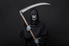 Death with scythe standing in the dark. Halloween Stock Photos