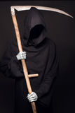 Death with scythe standing in the dark. Studio portrait on black background Stock Photos